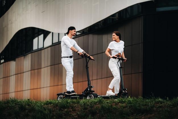 少女と男が街中の電動スクーターを歩いており、カップルはスクーターに恋をしています。