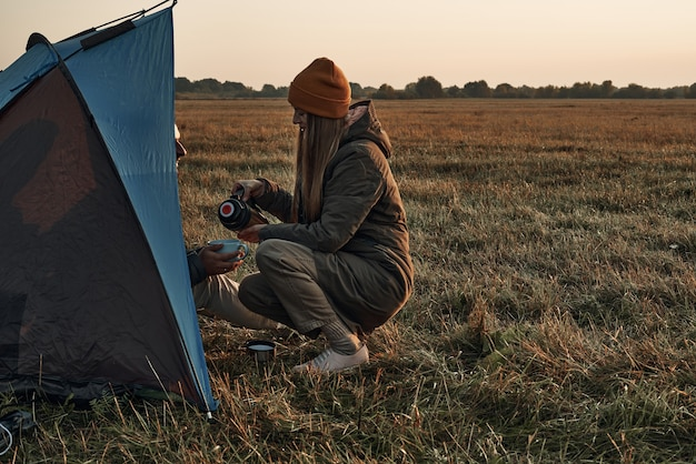 テントの中で女の子と男がマグカップから飲み、秋の時間、旅行。彼らは自然の中で夜明けに出会う。