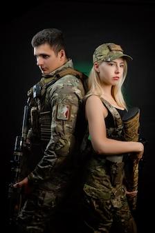 Девушка и парень в военной форме позируют со страйкбольным пистолетом на темном фоне