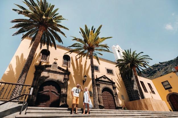 Девушка и мужчина гуляют по старому городу гарачико на острове тенерифе в солнечный день. семья гуляет по старому городу тенерифе на канарских островах. испания.