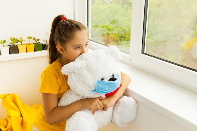창문 근처에 의료용 마스크를 쓴 소녀와 장난감 곰이 거리를 바라보며 전염병으로 인해 집에 머물 필요가 있습니다. 전염병의 맥락에서 격리 및 격리의 개념.
