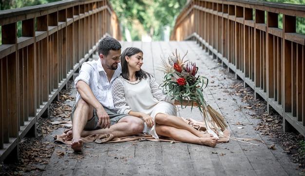 少女と若い男が橋の上に座って、コミュニケーション、自然の中でのデート、ラブストーリーを楽しんでいます。
