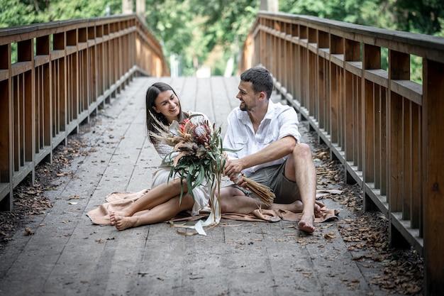 少女と青年が橋の上に座り、コミュニケーション、自然の中でのデート、ラブストーリーを楽しんでいます。