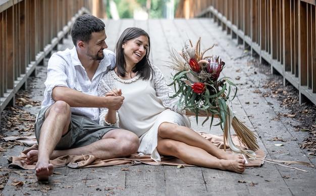 Девушка и молодой человек сидят на мосту и наслаждаются общением, свиданием на природе, историей любви.