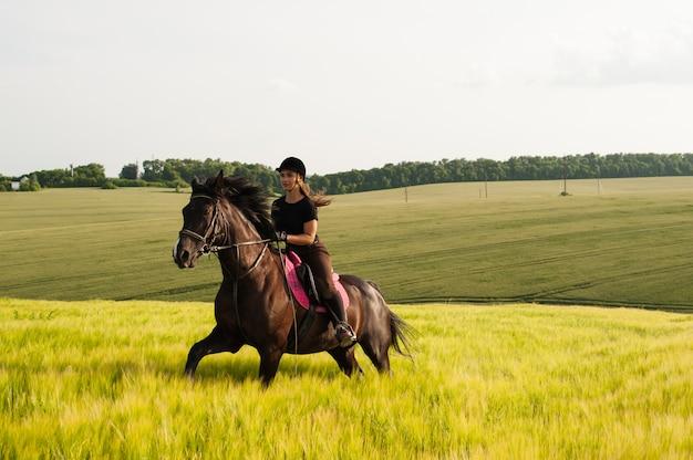 Девушка и молодая спортивная лошадка на природе