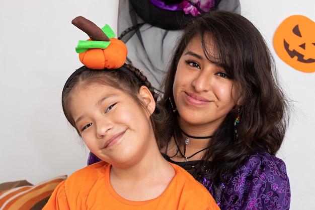 笑顔でカメラを見ている少女と若い女性が変装している