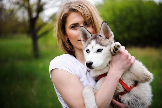 Девушка и ее собака хаски гуляют в парке