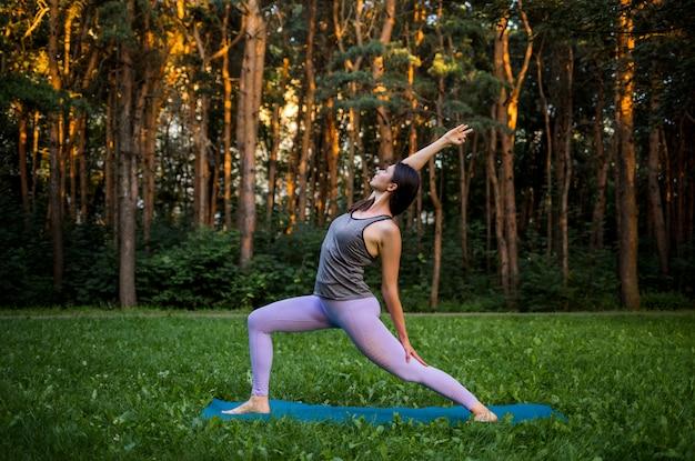 Девушка-спортсменка в спортивной форме занимается спортом на природе на закате