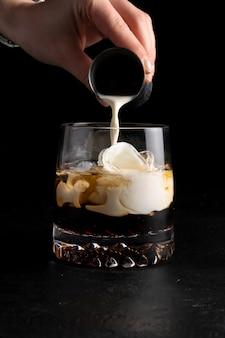 Девушка-бармен готовит коктейль «белый русский» и наливает в него сливки.