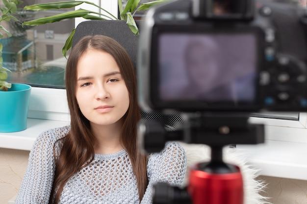 Девушка-блогер ведет видеоблог, общается с подписчиками перед камерой