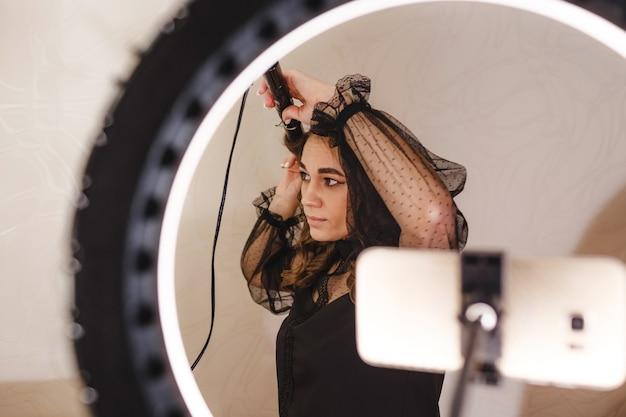 Девушка-блогер-парикмахер снимает на телефон видео и рассказывает своим зрителям, как правильно делать прически.