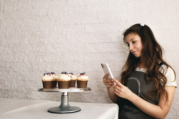 Девушка-блогер фотографирует на свой телефон торты и кексы для подписчиков