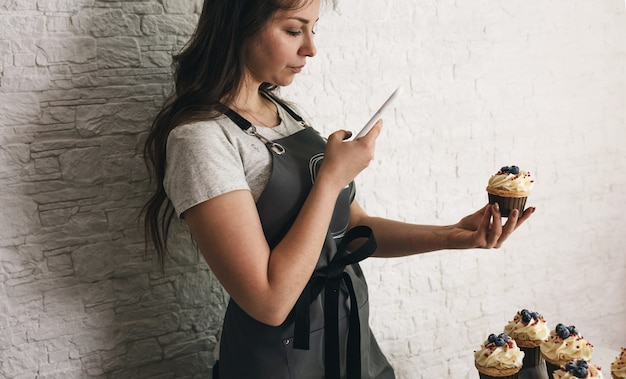 Девушка-блогер фотографирует на свой телефон вкусные торты и кексы для своих подписчиков.