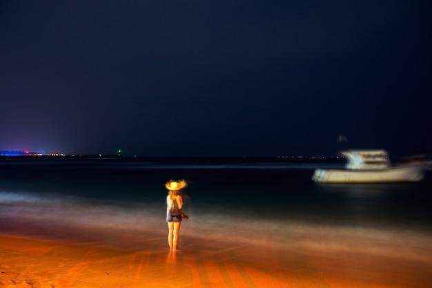 밤에 바다 옆에 있는 소녀, 긴 노출. 디포커스