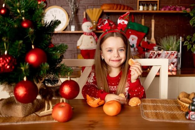 한 여자 아이가 새해와 크리스마스의 개념인 빨간 공이 있는 크리스마스 트리 옆에 있는 어두운 부엌에서 귤을 먹습니다.