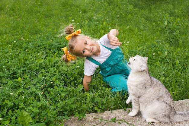 여자 아이는 고양이에게 풀을 먹인다