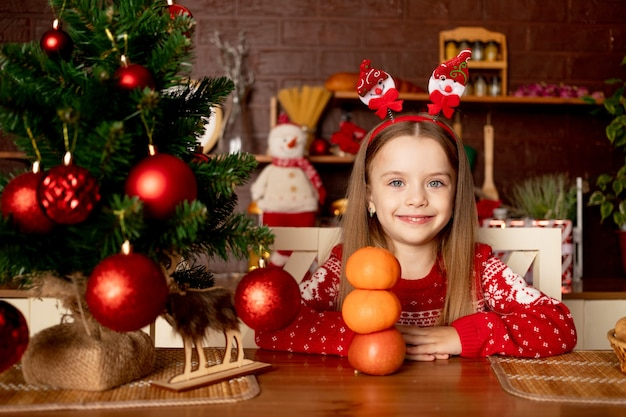 한 여자 아이가 귤에 탐닉하고 새해와 크리스마스의 개념인 빨간 공이 있는 크리스마스 트리 옆에 있는 어두운 부엌에서 눈사람을 돋보이게 합니다.