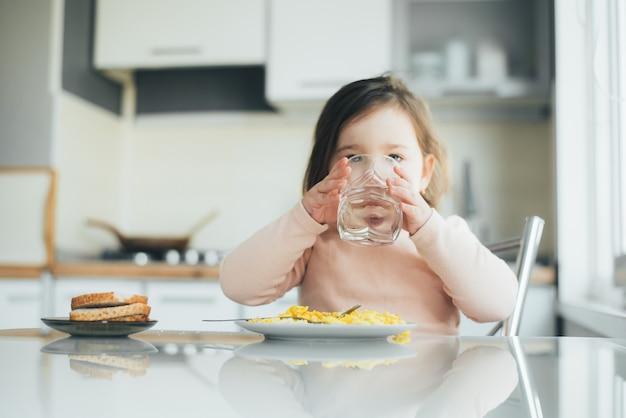 여자 아이가 부엌에서 물을 마시고 있고 옆에 오믈렛이 있는 접시가 있습니다