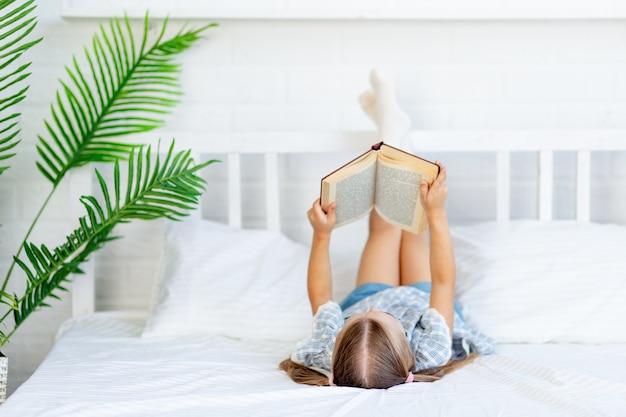 Девочка читает книгу на кровати дома на белой хлопчатобумажной кровати, лежа на спине