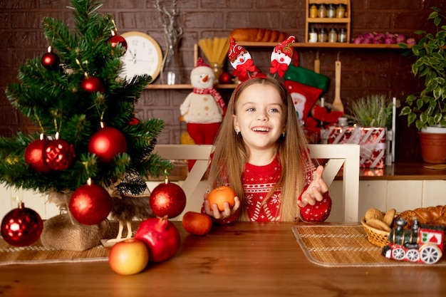 한 여자 아이가 새해와 크리스마스의 개념인 빨간 공이 있는 크리스마스 트리 아래 어두운 부엌에서 귤을 놀거나 먹습니다