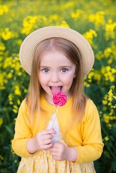 女児が畑を歩き、花、笑顔、菜種畑を集め、お菓子を食べる