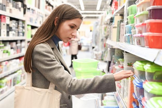 Девушка выбирает контейнер для еды в супермаркете.