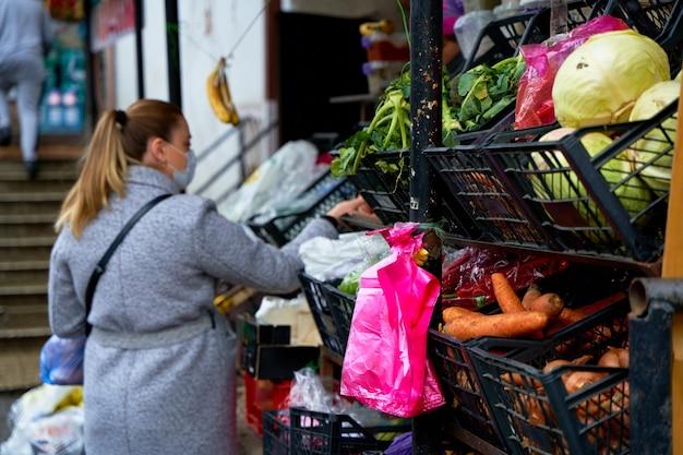 한 소녀가 길거리 야채 가게에서 물건을 고릅니다.