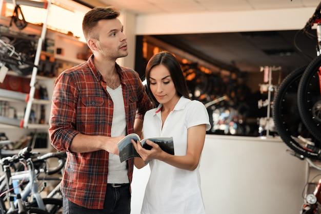 Девушка-консультант показывает покупателя в магазине велосипедов.