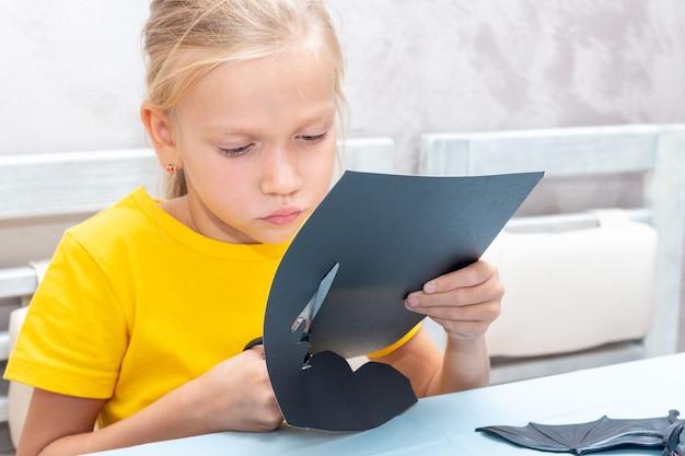 Девушка вырезает дома украшение на хэллоуин из черной бумаги. поделки для дома своими руками. ребенок делает поделки из бумаги, оригами