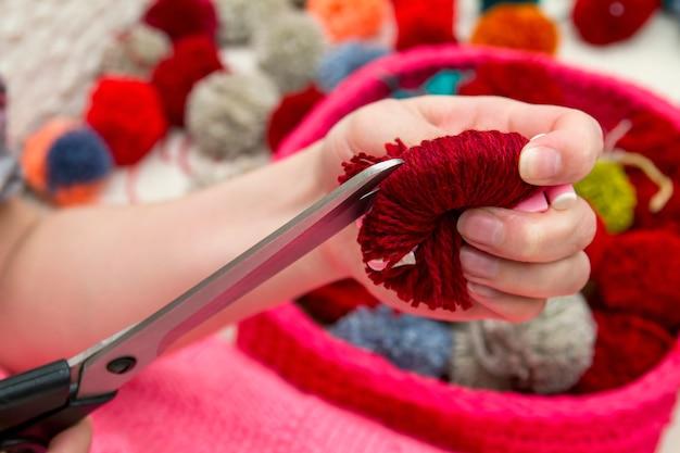 Девушка режет помпон ручной работы ножницами. процесс изготовления помпонов из ниток