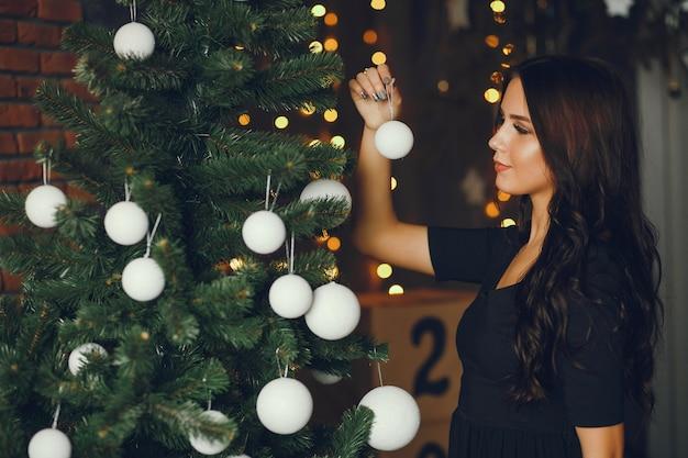 소녀는 크리스마스 트리를 장식합니다.