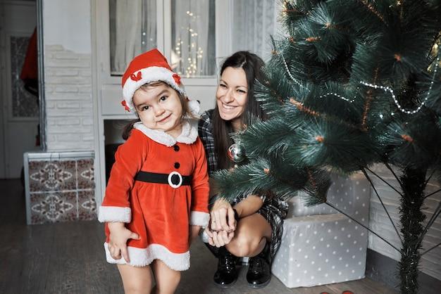 サンタクロースを装った女の子が笑顔のカメラをのぞき込む