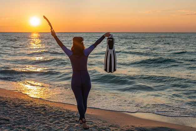 Девушка-дайвер на пляже на рассвете, поднимая руки вверх