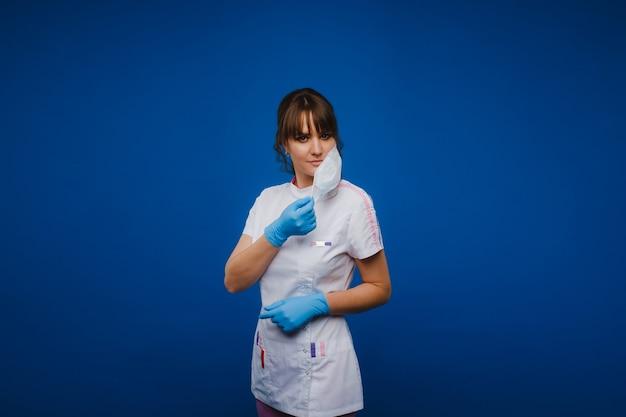 少女医師は、青い背景で隔離の医療マスクに立っています。