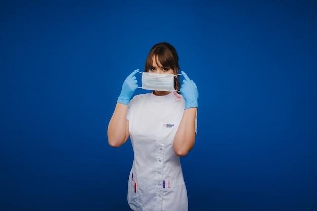 少女医師は、灰色の背景に隔離された医療マスクに立っています。