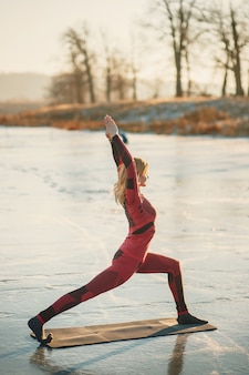 女の子は日没時に湖の氷の上で冬にヨガをします