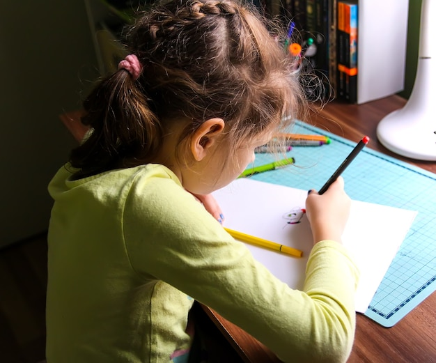 집에서 숙제를 하는 소녀.