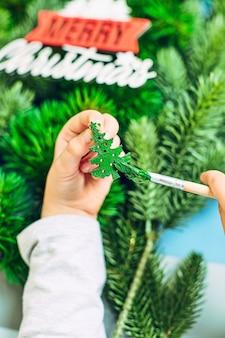 女の子がクリスマスツリーを描き、2022年の新年の準備をします。メリークリスマスと新年あけましておめでとうございますのコンセプト