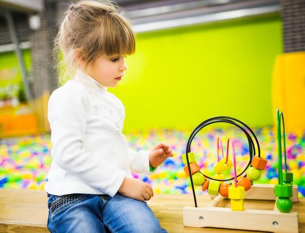 청바지와 흰색 스웨터를 입은 소녀가 놀이방에서 개발중인 나무 장난감을 가지고 놀고 있습니다.
