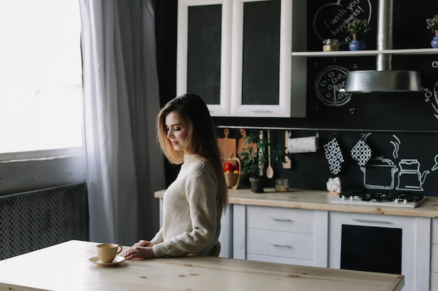Девушка пьет кофе на кухне дома по утрам