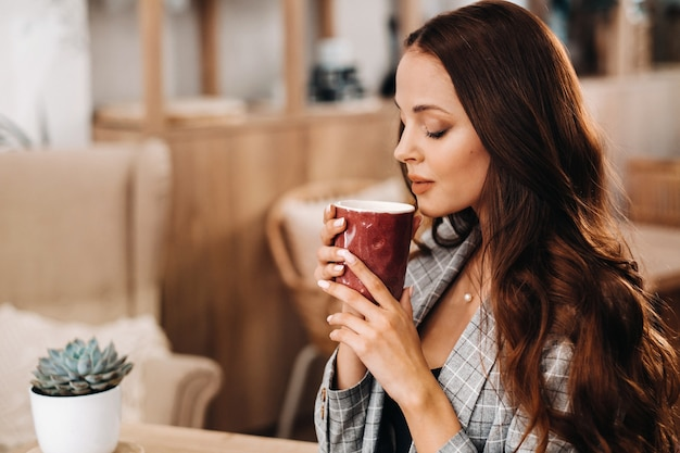 Девушка пьет кофе в кафе, красивые волосы девушки.
