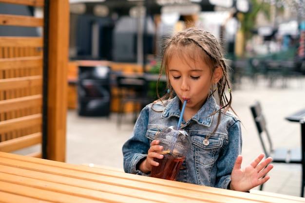 한 소녀가 도시 카페 테이블에 앉아 빨대로 레모네이드를 마신다