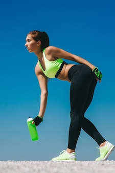 Девушка пьет воду после спорта