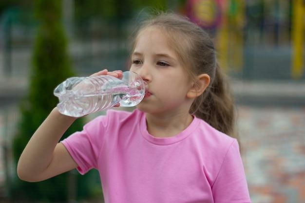 공원 놀이터에서 한 소녀가 병에서 물을 마신다