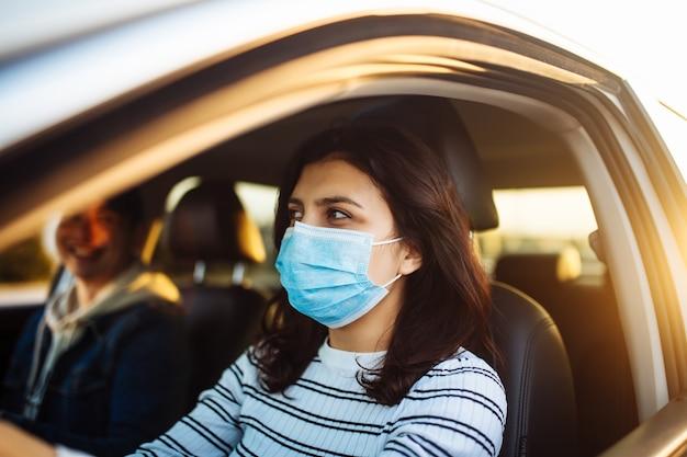 Девушка водит машину с пассажиром в медицинской маске во время карантина по пандемии коронавируса