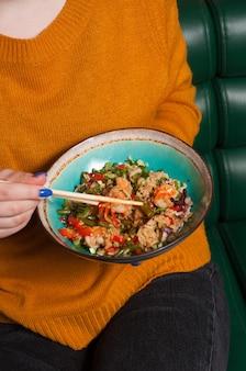 Девушка ест чесночный рис с креветками в ресторане
