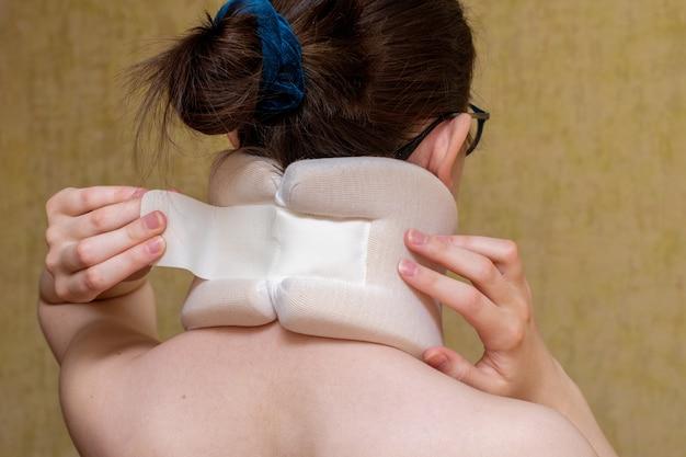 Девушка застегивается хирургическим воротником на шею, страдает от боли в шее, вид со спины