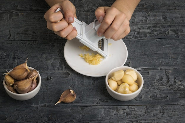 女の子は木製のテーブルのおろし金でニンニクをすりおろします。キッチンに人気のスパイス。