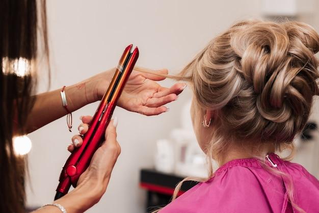 Девушка-парикмахер делает прическу клиентке на праздник с помощью утюжка-выпрямителя.