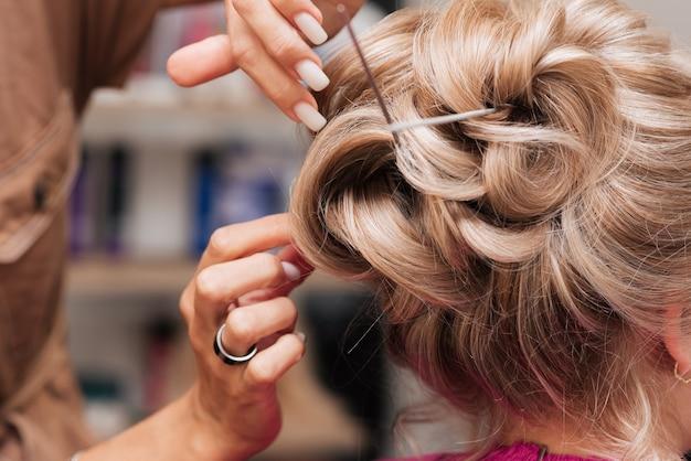 Девушка-парикмахер делает прическу клиентке к торжеству, закалывая пряди шпильками и шпильками.